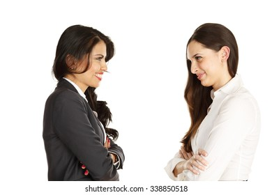 Two business woman with arms crossed. Looking at each other with emotions ranging from confrontational to joyous laughter. Also looking at camera.