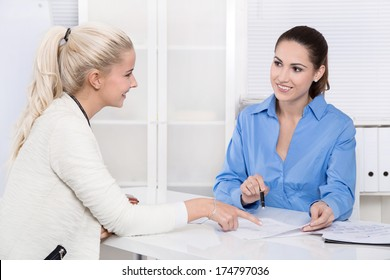 Two business woman at desk - application or interview - talking together.