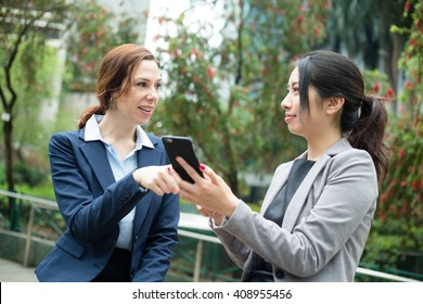 Two business woman discuss on cellphone