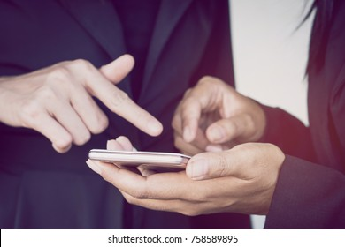two business woman looking at mobile phone talking about their project while working together at office