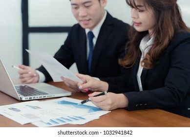 two business woman and business man investment consultant analyzing company annual financial report balance sheet statement working with documents graphs. Concept picture of economy, market, money