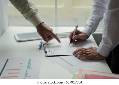two business woman and business man investment consultant analyzing company annual financial report balance sheet statement working with documents graphs