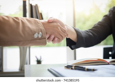 Two business woman shaking hands during a meeting to sign agreement and become a business partner, enterprises, companies, confident, success dealing, contract between their firms.