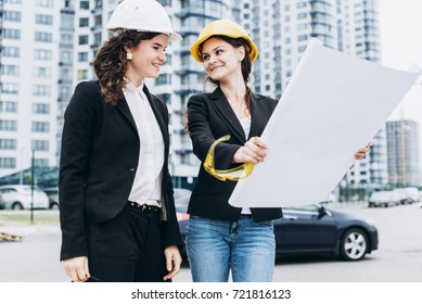 Two business women in building helmets and safety glasses looking at building schemes, architectural concept