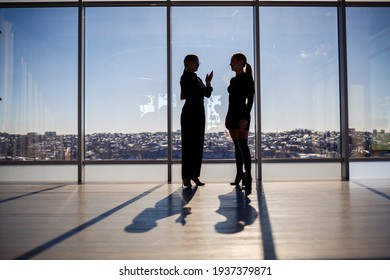 Two business women enjoying the city view and talking while standing by the large window in the office