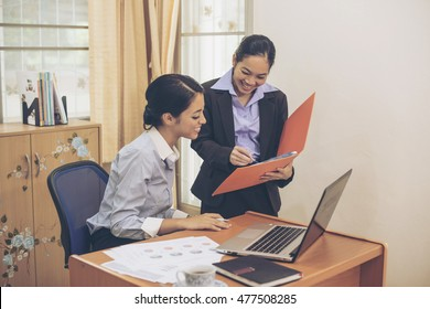 Two business women are examining the company's financial report .