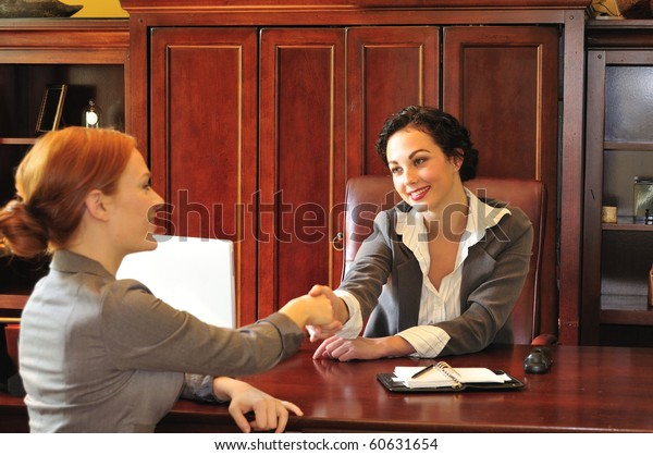 two business women greeting each other in an office meeting