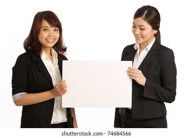 Two business women holding a sign