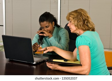 Two business women look at a laptop in an office conference room, one of the women yawns as if tired or bored with the work.