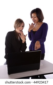 Two business women looking at something on the computer with surprised expressions on their faces.
