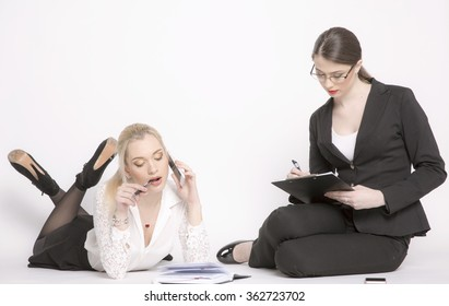 Two business women on a white background. Girl in costumes sit and work.