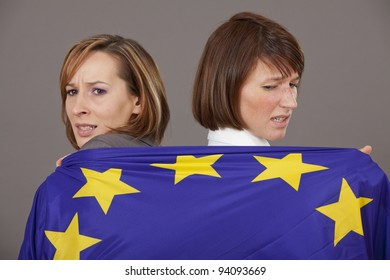 two business women pulling on european flag to each side