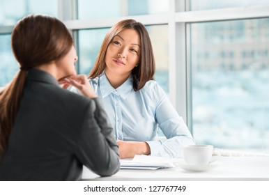 Two business women talking and signing contract at office