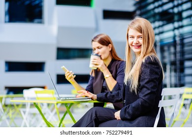 Two business women working in a in terrace cafeteria. Education, lifestyle and people concept.