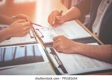 Two business worker are consulting on company data document on table