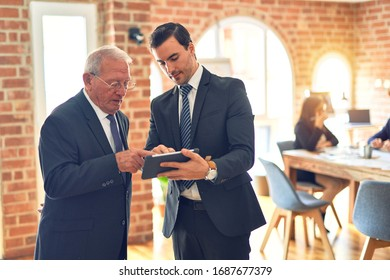 Two business workers working together. Speaking and using tablet standing at the office