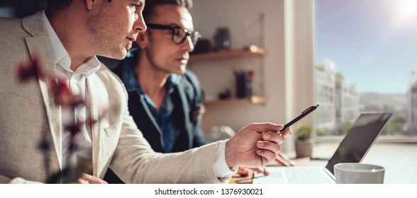 Two businessman analyzing data report on the laptop in office
