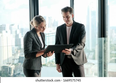 Two businessman and businesswoman couple meeting in co working space at sky lounge