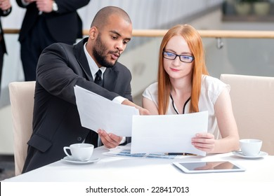 Two businessman discussing documents. Four smiling successful businessmen sitting at table in office while discussing their of business doings. Young people talking in office