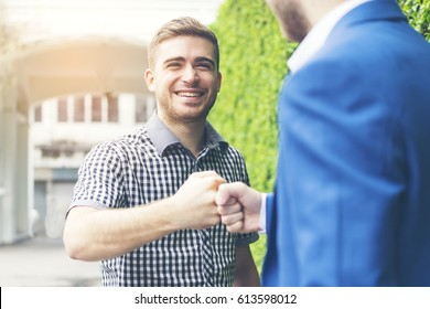 Two businessman giving fist bump or handshake after business achievement, work togetherness or collaboration to win project - teamwork concept