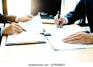 Two businessman  hold pen on their hand, business team in a small meeting in the office talk about  analyses chart graphy marketing plan with computer laptop.