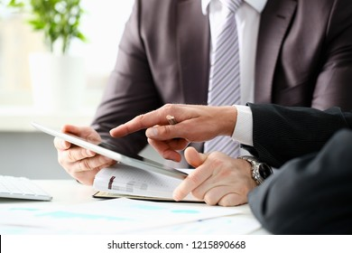 Two businessman are looking and studying statistics on tablet display closeup. Male hand opponent holds pen and points out problem collaboration business coach cooperation partnership palm concept
