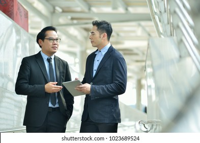Two businessman people are discussing new project. Present to the management to approve this project.