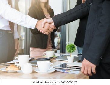 Two businessman shaking hand on open space office at cafe. Selective focus.
