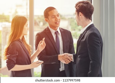 Two businessman shaking hands with a woman secretary/translator standing on the side.