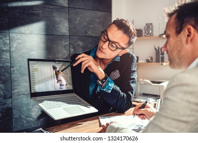 Two businessman sitting by the desk and analyzing project timeline on a meeting in the office