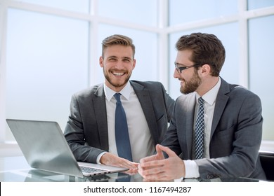 two businessman sitting at his Desk
