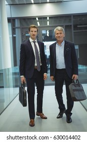 Two businessman standing in corridor at office