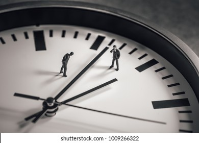 Two businessman standing in the middle of clock face. Business concept.
