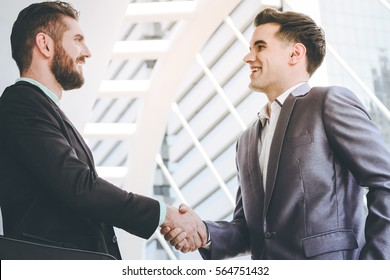 Two businessman talking and shaking hands outdoors at sidewalk of modern office building