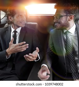 two businessman talking while sitting in the car