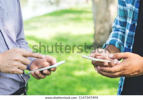 Two businessman using smartphone in the park.