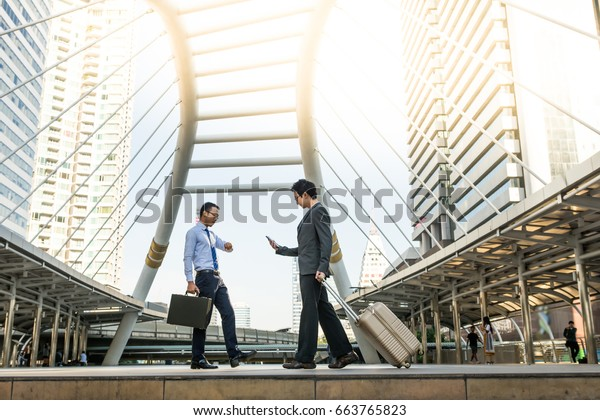 Two businessman walking in the city in a rush time, one is looking at his mobile phone and carrying travel suitcase, the other is holding briefcase  and looking at his watch on his hand