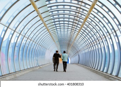 Two businessman walking in the modern tunnel. United Kingdom, London, Canary Wharf area.