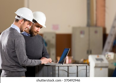 Two businessman working with laptop in factory.