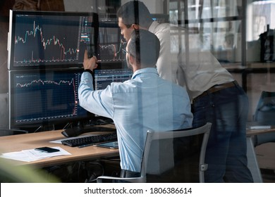 Two businessman working in office together, pointing at screen, discussion and checking global currency index on fund exchange