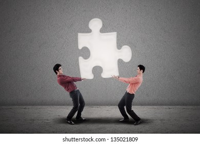 Two businessmen carry a puzzle together on grey background