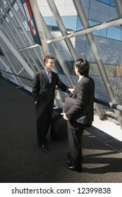 Two businessmen chatting in the lobby of an office building