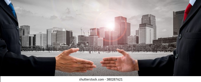 Two businessmen in dark gray suit going to make handshake and deal for their business and future success. City scape and sunshine in the background