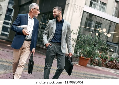 Two businessmen discussing about the new project while walking outdoors.