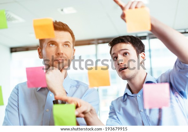 Two businessmen discussing ideas written on sticky notes