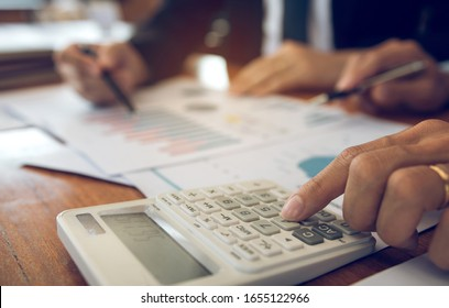 Two businessmen discussion analysis sharing calculations about the company budget and financial planning together on desk at the office room.