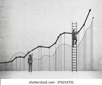 Two businessmen drawing graphs on a concrete wall, one of them on a ladder. Back view. Concrete background. Concept of analysing information.