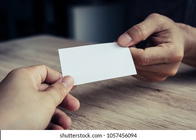 Two businessmen exchanged business cards on a wooden table. White business cards. Copy space.