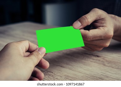 Two businessmen exchanged business cards on a wooden table. Green screen business cards. Copy space. Vintage Style. Business Concepts.