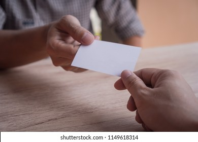 Two businessmen exchanged business cards on a wooden table. Introduction and Exchange of Connections. White business cards. Copy space.